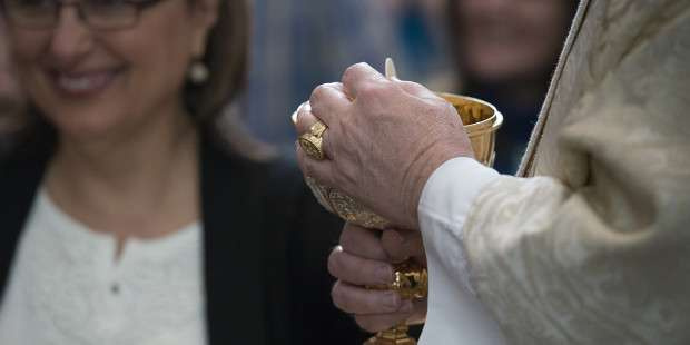 """At Communion, my priest says, """"Receive Jesus Christ"""" instead of """"The body of Christ."""" Is this OK?"""