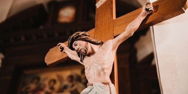 Why do Catholics use crucifixes that show Jesus on the cross?
